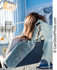 Back view of young female patient visiting dentist office sitting at dental chair. Clinic stomatology