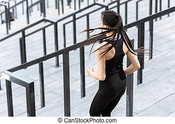 Back view of young fitness woman in sportswear exercising on stadium stairs
