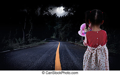 Back view of young girl is standing on road in a forest. Lonely child with doll sad gesture.