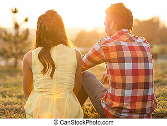 back view of young happy couple sitting on river. honeymoon conc