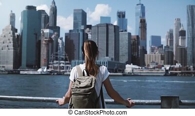 Back view of young happy tourist girl with backpack and arms...