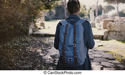 Back view of young happy woman with backpack walking with a map along ancient ruins in Ostia Antica, Italy on vacation.