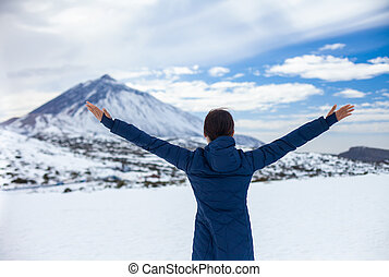 Back view of young happy woman with hands up enjoying snow mountains with volcano El Teide on background