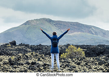 Back view of young happy woman with hands up enjoying unique volcanic landscapes