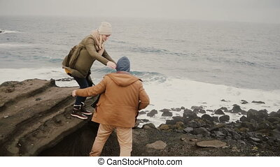 Back view of young man and woman standing on the shore of the sea in cold day, holding hands and looking on water.