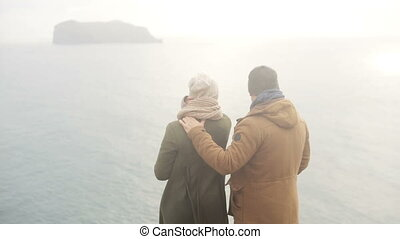 Back view of young man and woman standing on the shore of the sea and enjoying the beautiful view in cold foggy day.