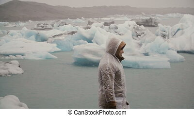 Back view of young man in raincoat standing in ice lagoon in...