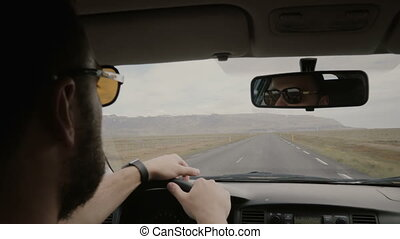 Back view of young man in sunglasses driving the vehicle,...