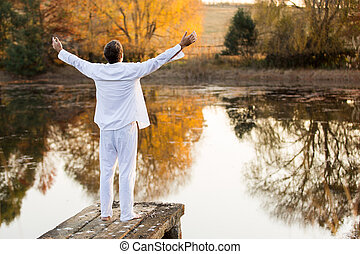 young man standing on pier with arms outstretched - back...