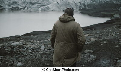Back view of young man walking in ice lagoon alone....