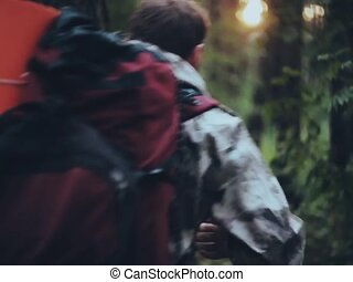 Back view of young man with backpack in camouflage unionalls walking through forest. Tourist male going to camping trip.