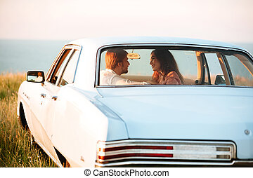 Back view of young pretty couple in car