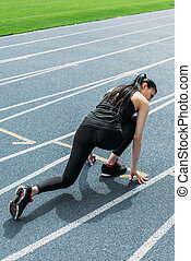 Back view of young sportswoman in starting position on running track stadium