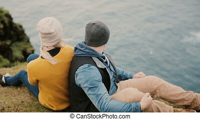 Back view of young stylish couple sitting at the edge of the cliff and looking on sea, enjoying the beautiful landscape.