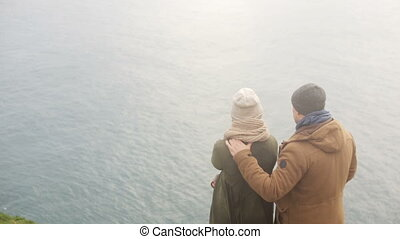 Back view of young stylish couple standing on the shore of the sea and enjoying the beautiful landscape together.