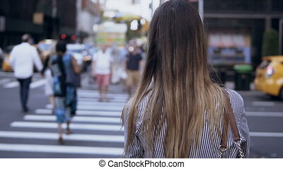 Back view of young stylish woman walking in the downtown, female crossing the road, going through the crowd in New York