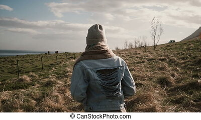 Back view of young stylish woman walking through the field near the river. Female in the horses ranch in Iceland.