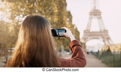 Back view of young teenager female using smartphone to...