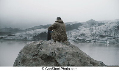 Back view of young tourist sitting on the rock and looking on the glaciers in ice lagoon. Man exploring Iceland alone.