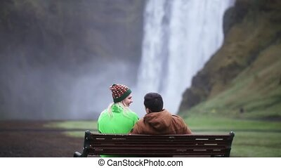 Back view of young tourists couple resting near the waterfall Skogafoss in Iceland. Man and woman on the bench.