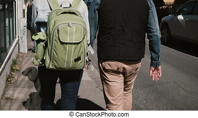 Back view of young tourists couple walking through the street in bright sunny day. Man and woman on a romantic date.