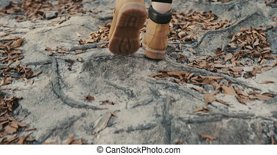 Back view of young traveler girl leg walking at rocks, woman tourist walking woods