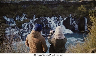 Back view of young traveling couple standing in mountains near the waterfalls in Iceland and taking photo on smartphone