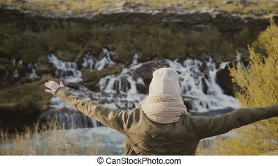 Back view of young traveling woman raising hands up and enjoying the beautiful view of waterfalls in Iceland.