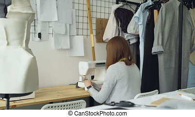 Back view of young woman clothing designer working with...