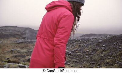 Back view of young woman hiking in rocky hills. Traveling...