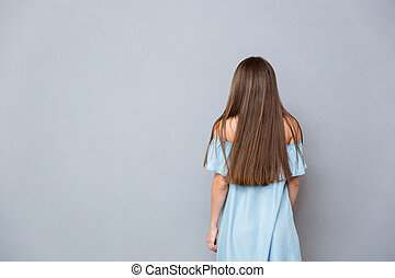 Back view of young woman in blue dress