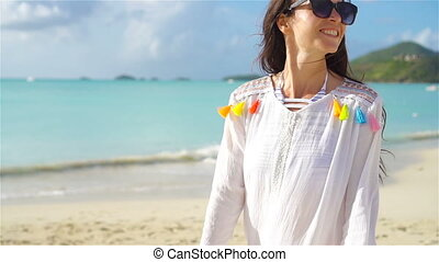 Back view of young woman on tropical white beach. SLOW MOTION