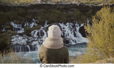 Back view of young woman standing in mountain valley and looking on waterfalls in Iceland, exploring the nature.