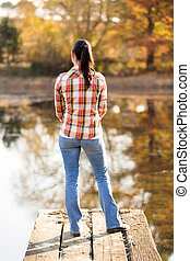 back view of young woman standing on lake pier