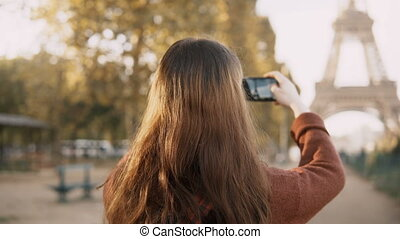 Back view of young woman taking photos on smartphone. Teenager tourist exploring the Eiffel tower in Paris, France.