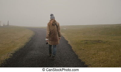 Back view of young woman walking through the field alone....