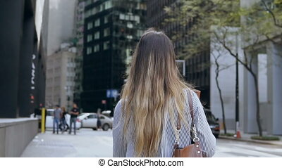 Back view of young woman with documents going to work in office building in financial district of New York. Slow motion.