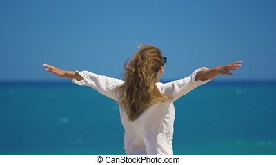 Back view of young woman with wind in her hair raising her...