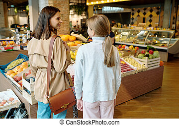 Back view of youthful girl and her mother deciding what to buy in supermarket