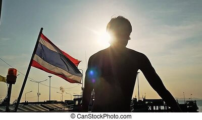 Back view ofyoung man standing on pier next to thai flag enjoying sunny day during amazing sunset with lens flare effects. slow motion.