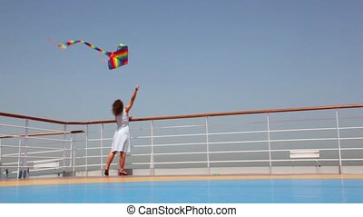 back view on woman flying a kite on deck