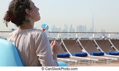 back view on young beautiful woman sitting on deck of ship and drinking cocktail