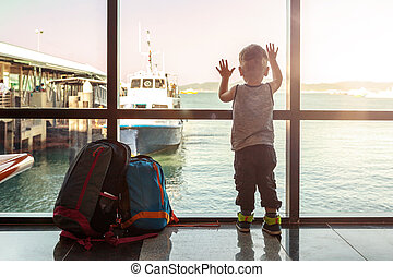 Back view on young boy in dock looking on boats.