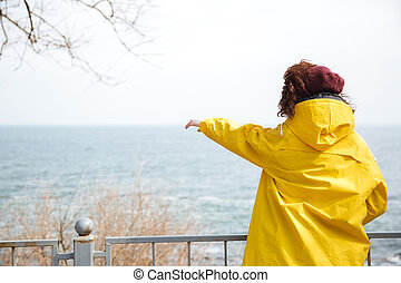 Back view ow woman in raincoat - Woman in yellow raincoat...