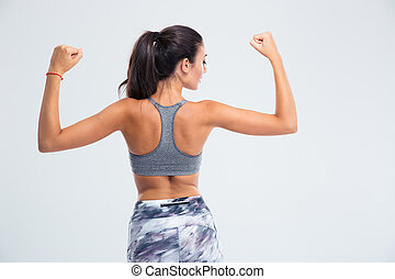 Back view portrait of a fitness woman showing her biceps