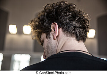 Back view portrait of a man with curly hair