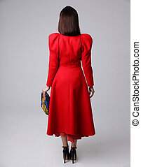 Back view portrait of a woman in red dress on gray background