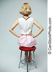 Back view portrait of a woman sitting on the chair over gray background