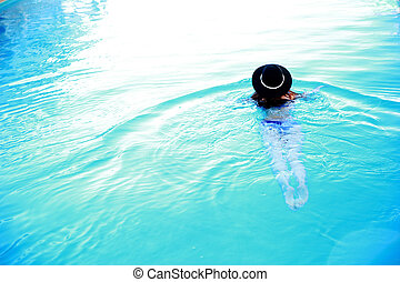 Back view portrait of a woman swimming in the pool