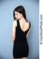 Back view portrait of a young woman in black dress